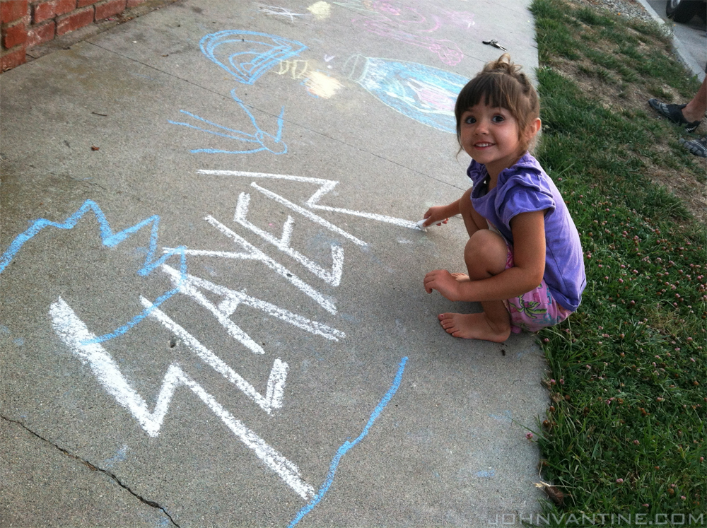Makena drawing the Slayer logo in sidewalk chalk.
