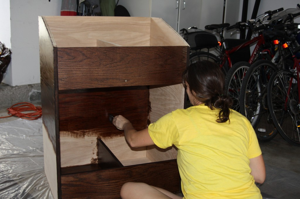 Lauren applying a polyurethane finish to the record storage bin